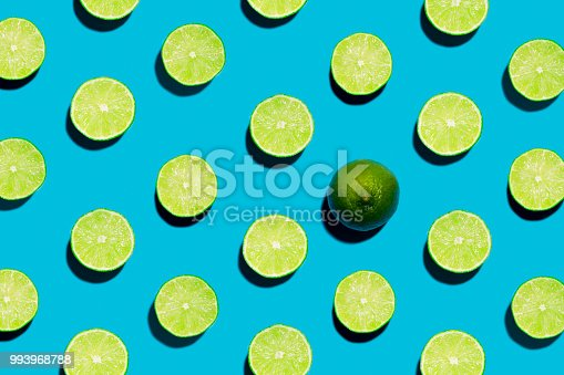 This is a fun brightly lit and colorful overhead photograph of sliced open geen limes lined in rows with a harsh shadow on a blue background.. There is one whole lime symbolizing individuality and being unique, different  or creative.