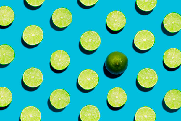 Sliced Open Geen Limes on Symmetrical Blue Background with one peeled open This is a fun brightly lit and colorful overhead photograph of sliced open geen limes lined in rows with a harsh shadow on a blue background.. There is one whole lime symbolizing individuality and being unique, different  or creative. lime stock pictures, royalty-free photos & images