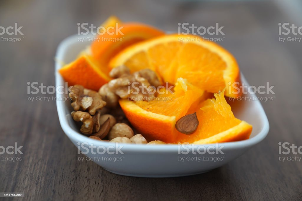 Sliced orange and nuts together in a bowl royalty-free stock photo