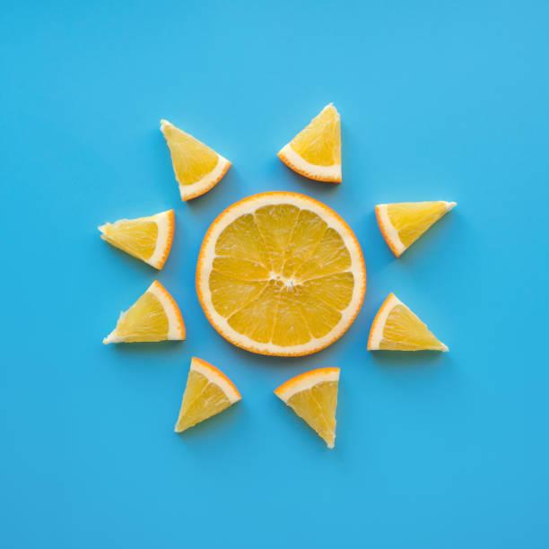 sliced orange fruit. sunny weather theme. - orange fruit stock photos and pictures
