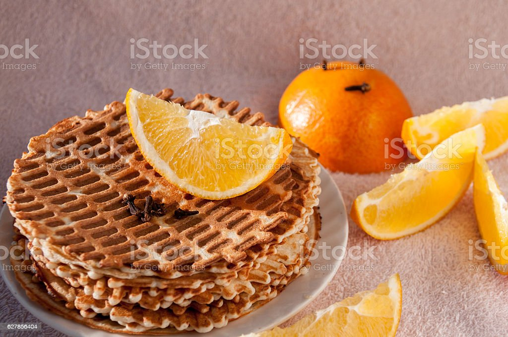 Sliced orange lies on homemade waffles stock photo