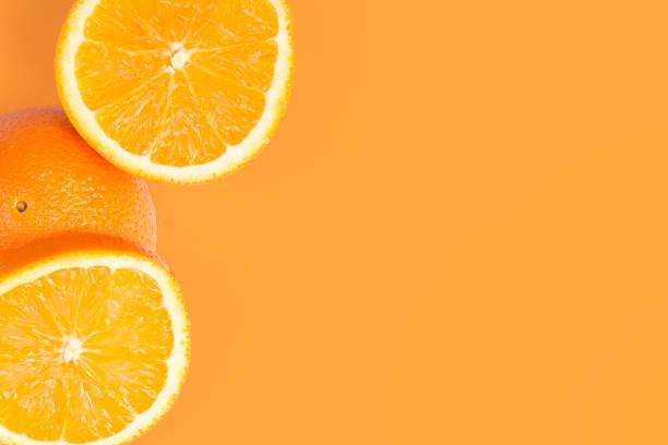 gesneden oranje op oranje achtergrond - vitamine c stockfoto's en -beelden
