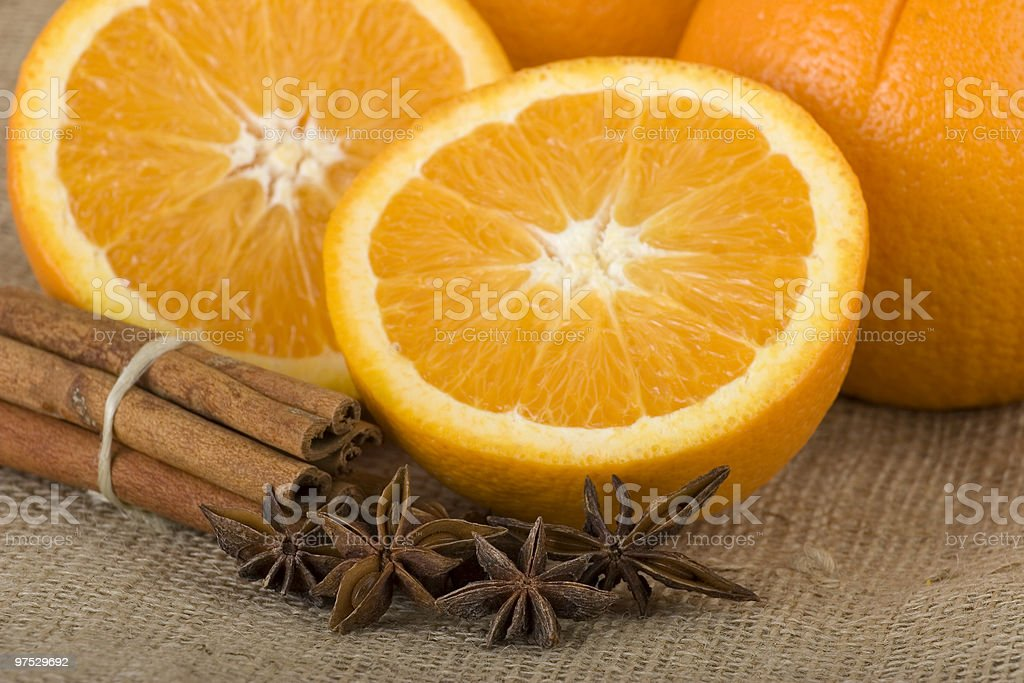 Sliced oranges next to a bundle of cinnamon sticks royalty-free stock photo