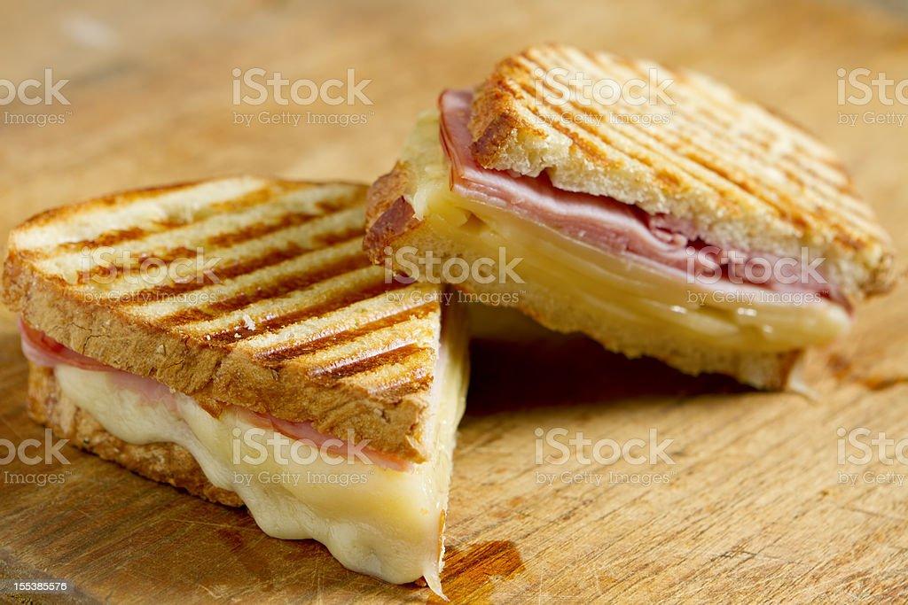 Sliced panini sandwich on wood surface stock photo