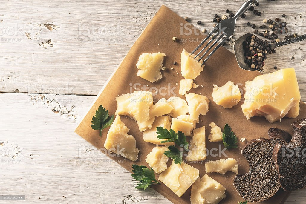 Sliced parmesan with bread , parsley and black pepper on  parchment stock photo