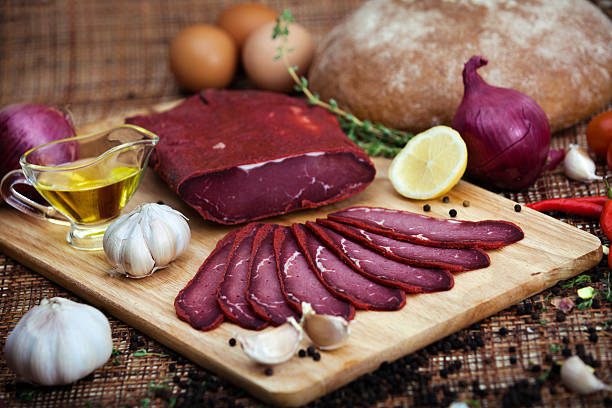 sliced pastrami on a chopping board - pastrami stock pictures, royalty-free photos & images