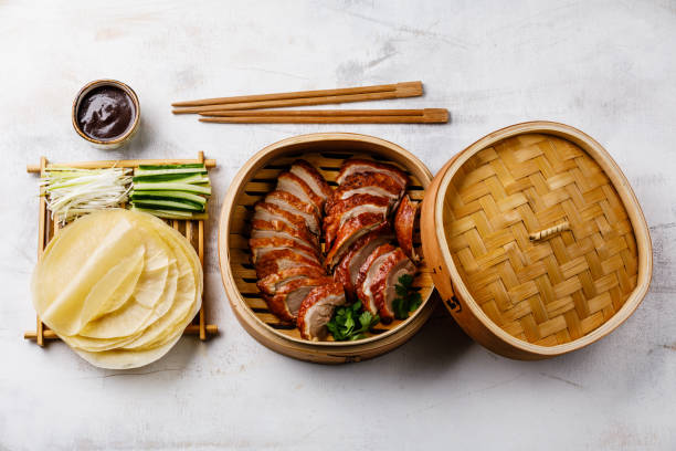 Sliced Peking Duck in bamboo steamer served with fresh cucumber, onion, Hoysin sauce and roasted wheaten pancakes