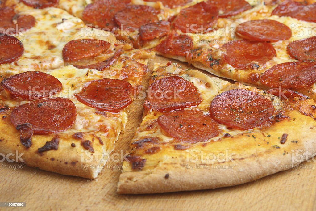 Sliced pepperoni pizza with one slice pulled away stock photo