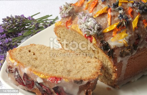 cake decorated with edible flowers, one cut slice with lavender in the background