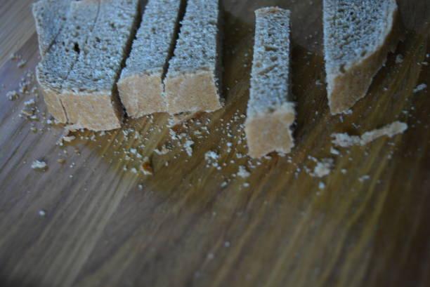 geschnittenes stück graues brot für cracker auf einem holzbrett.  gesunde lebensmittel, nahrung für jeden tag. - schwarzwurzeln kochen stock-fotos und bilder