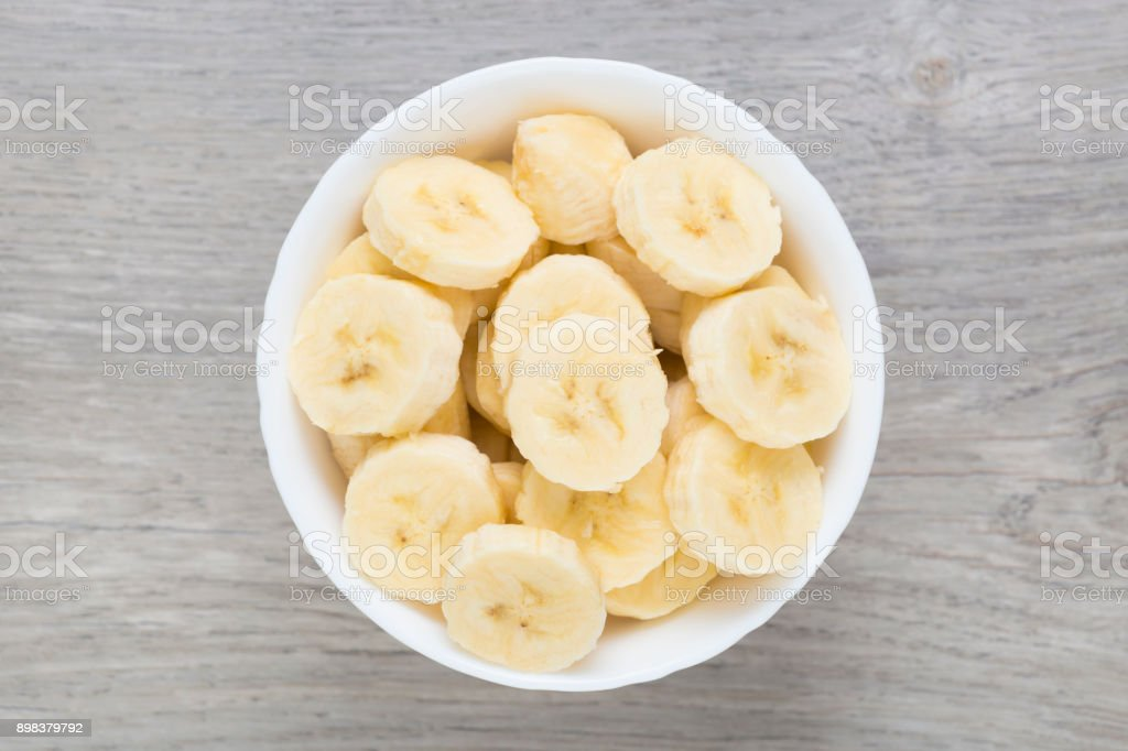 Sliced pieces of banana in white bowl. Directly above view. stock photo