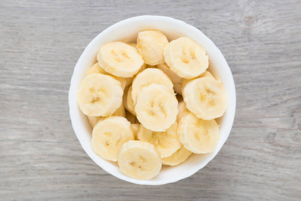 Sliced pieces of banana in white bowl. Directly above view. Bananas. banana stock pictures, royalty-free photos & images