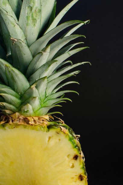 sliced pineapple fruit close up, black background stock photo