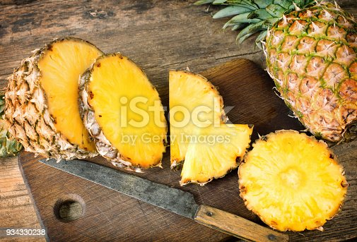 one whole and one sliced pineapples on wooden background
