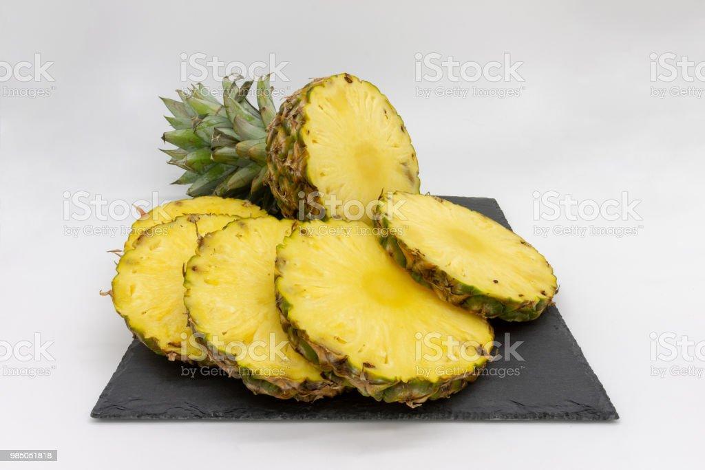 sliced pineapple served on a slate board stock photo