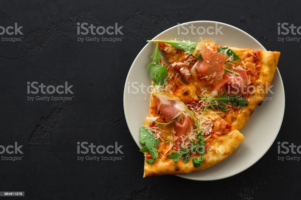 Sliced pizza with prosciutto and rocket salad royalty-free stock photo