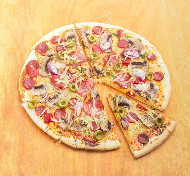 scheiben pizza mit wurst, champignons und oliven auf schneidebrett - gebackene champignons stock-fotos und bilder