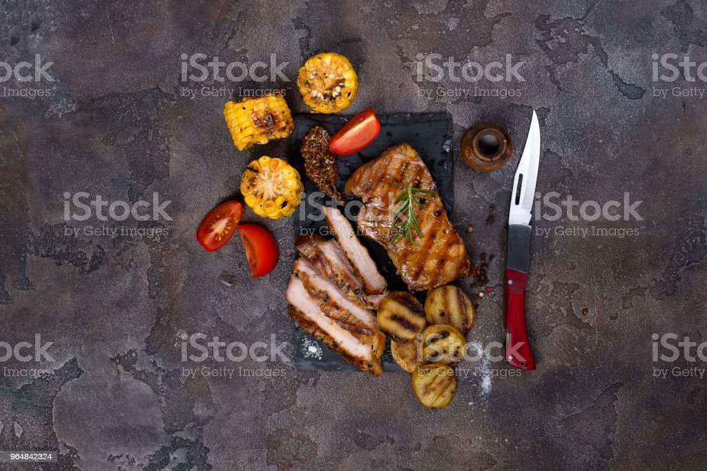 sliced pork steak and grilled vegetables on slate board on stone table. royalty-free stock photo