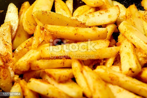 Sliced potato with spices. Cooking fried potatoes in a pan.