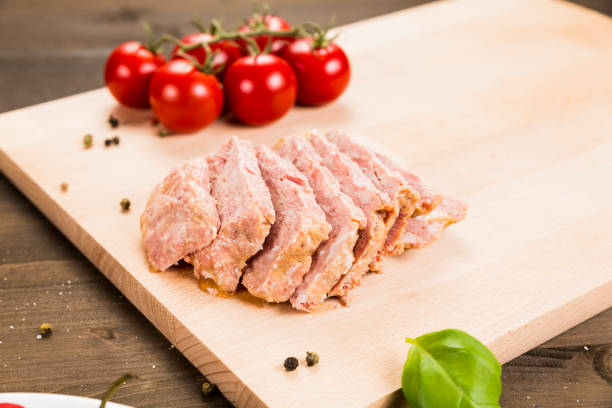 Sliced preserved ham on a cutting board stock photo