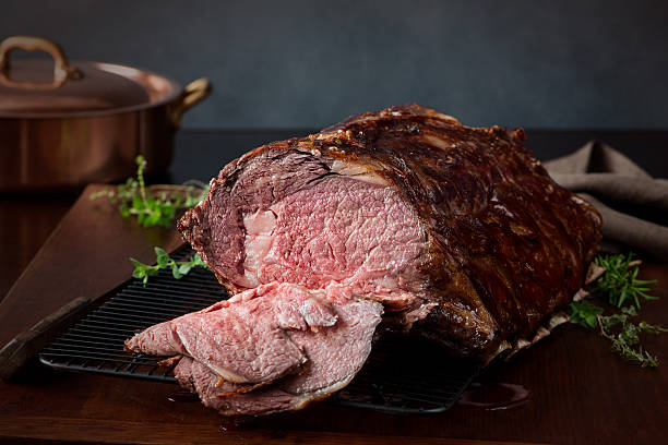 Sliced Prime Rib Roast - XXXL A prime rib roast beef, sliced open to show medium rare meat.  Very shallow DOF. roasted prime rib stock pictures, royalty-free photos & images