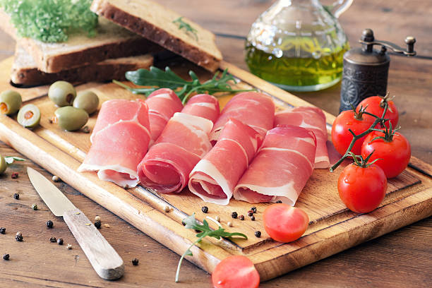 sliced prosciutto on a wooden board stock photo