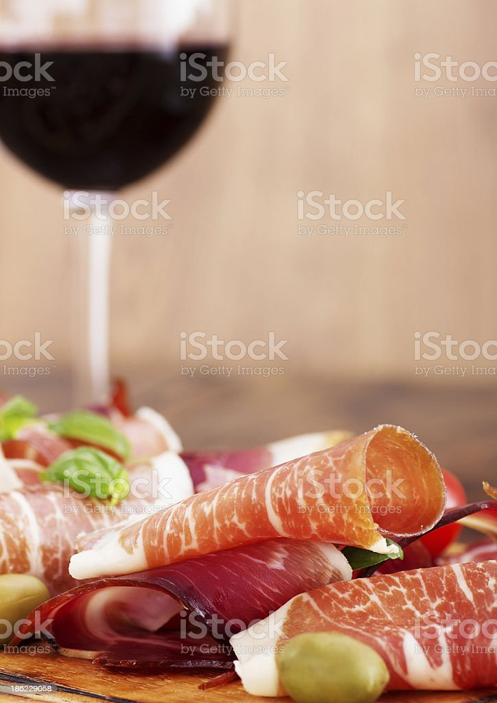 sliced prosciutto with red wine and olives stock photo