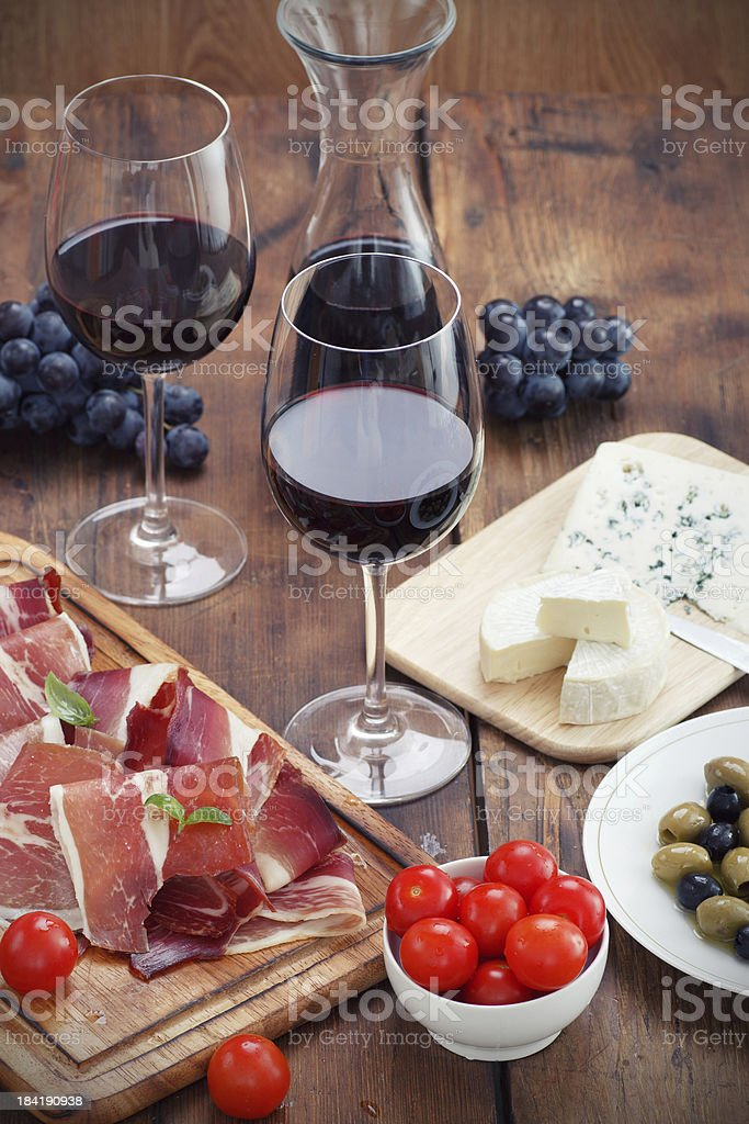 sliced prosciutto with red wine cheese and olives stock photo