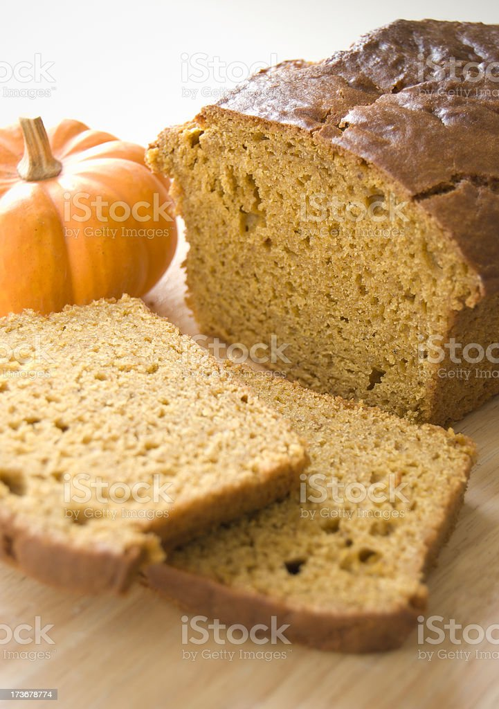 Sliced pumpkin bread loaf on wooden surface stock photo