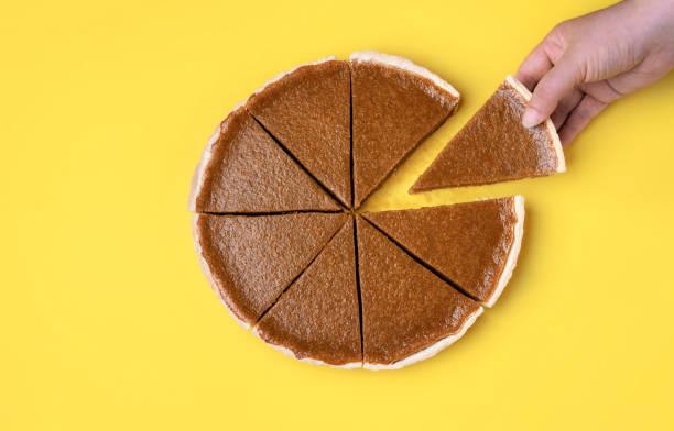 gesneden pompoen taart. het nemen van een cirkelsegment. - taart stockfoto's en -beelden