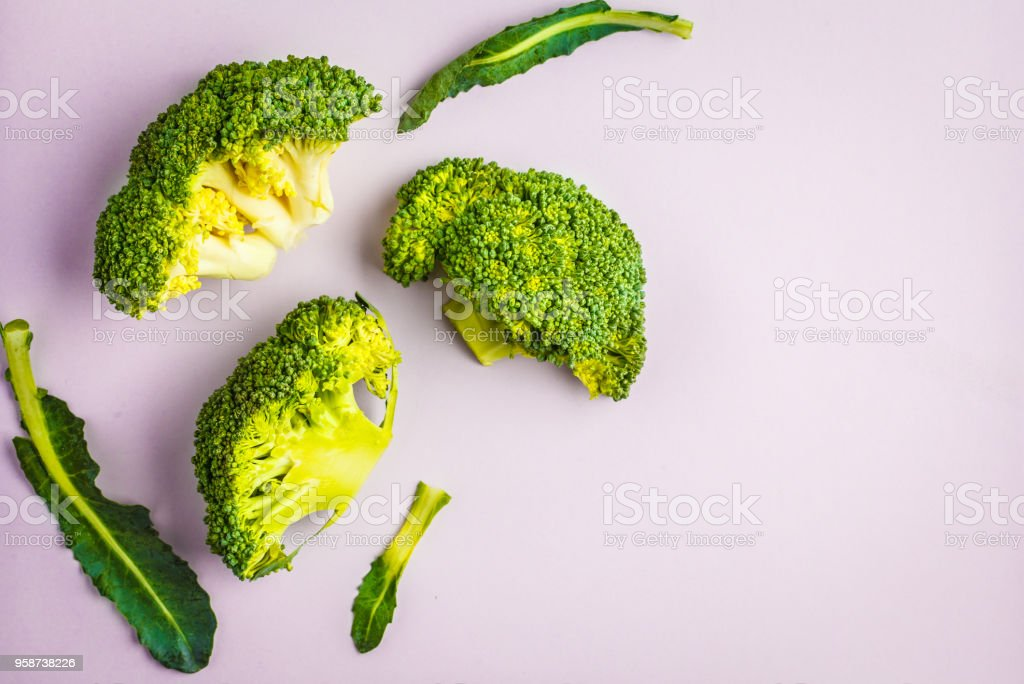 Sliced raw broccoli isolated on a pink background. Healthy vegan food concept. stock photo