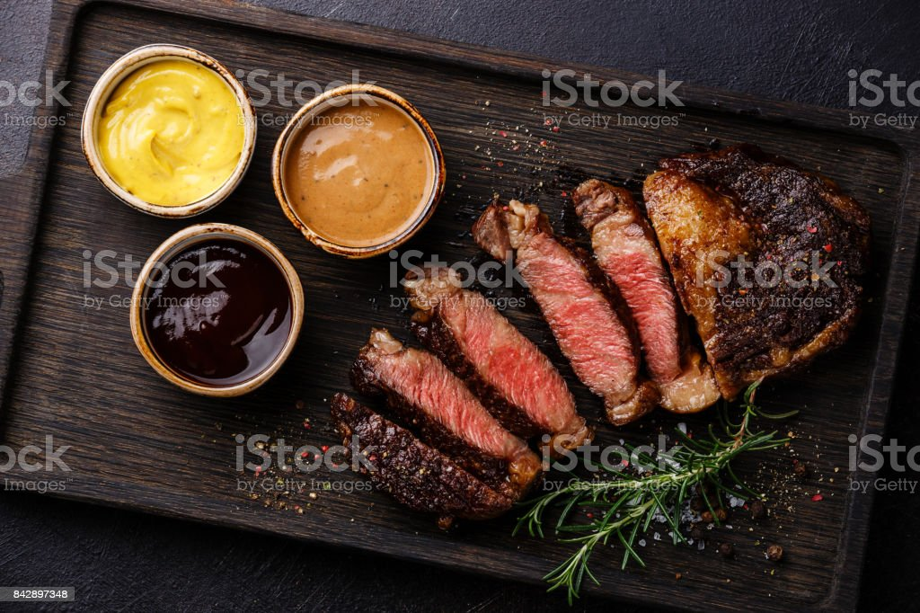 Sliced Rib eye steak and three different sauces stock photo