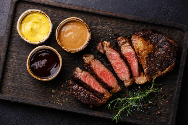 sliced rib eye steak and three different sauces - musztarda zdjęcia i obrazy z banku zdjęć