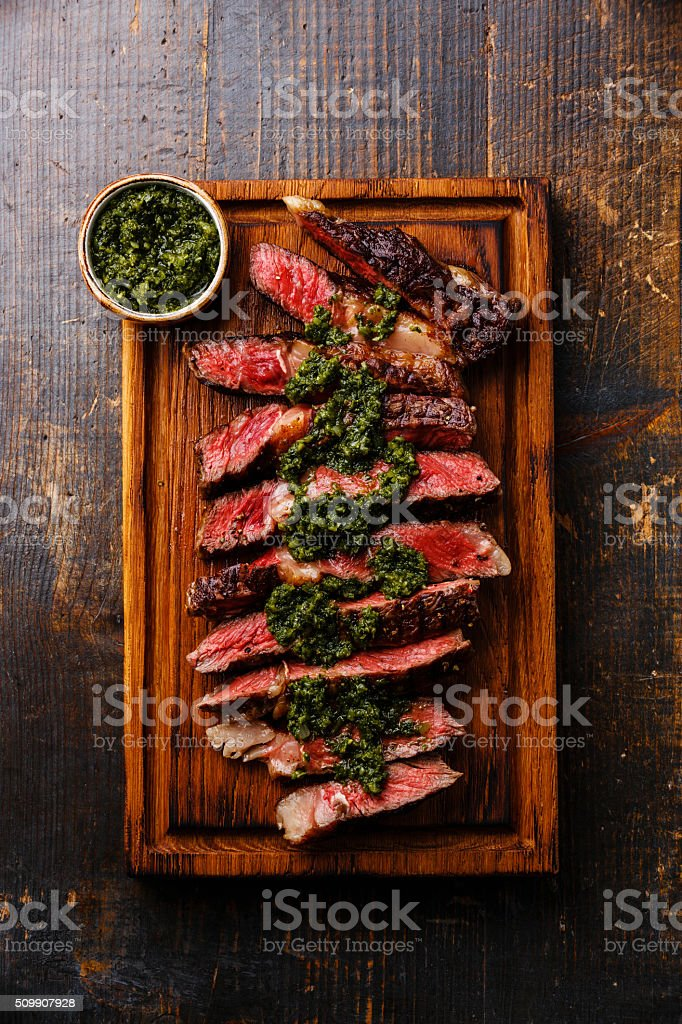 Sliced Ribeye steak with chimichurri sauce stock photo