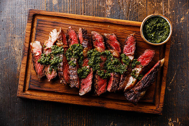Sliced Ribeye steak with chimichurri sauce Sliced medium rare grilled beef barbecue Ribeye steak with chimichurri sauce on cutting board on dark background rib eye steak stock pictures, royalty-free photos & images
