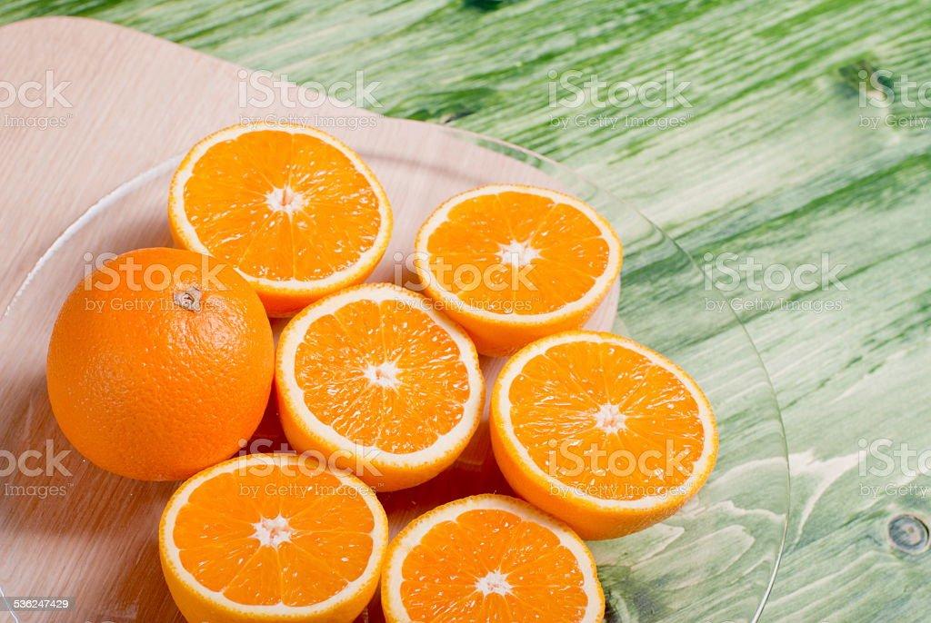 sliced ripe appetizing orange on a cutting board on agreen stock photo