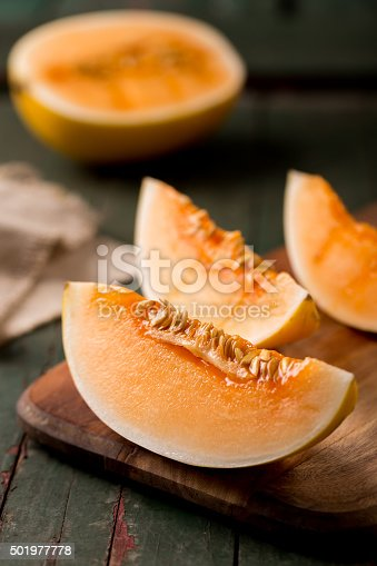 sliced ripe melon on a cutting board on rustic wooden background