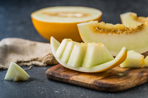 istock sliced ripe melon on rustic wooden background 614872530