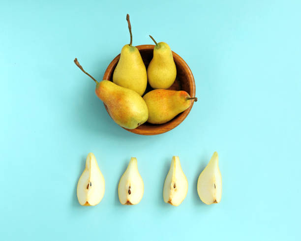 Sliced ripe pear on a plate and whole pears on blue background. stock photo