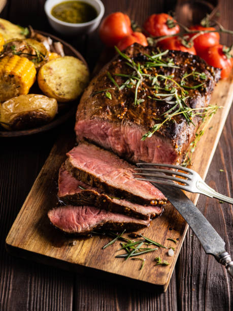 Cтоковое фото Sliced Roast beef on cutting board with grilled vegetables .