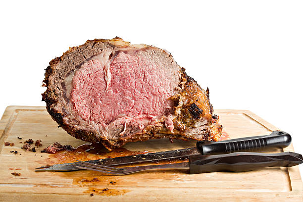 Sliced Roasted Prime Rib With Knife On Plank Sliced roasted prime rib on wooden plank isolated. roasted prime rib stock pictures, royalty-free photos & images