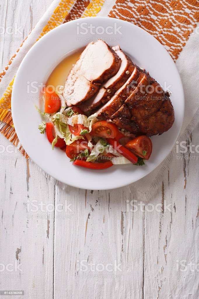 Sliced roasted turkey breast and fresh vegetables. vertical top view stock photo