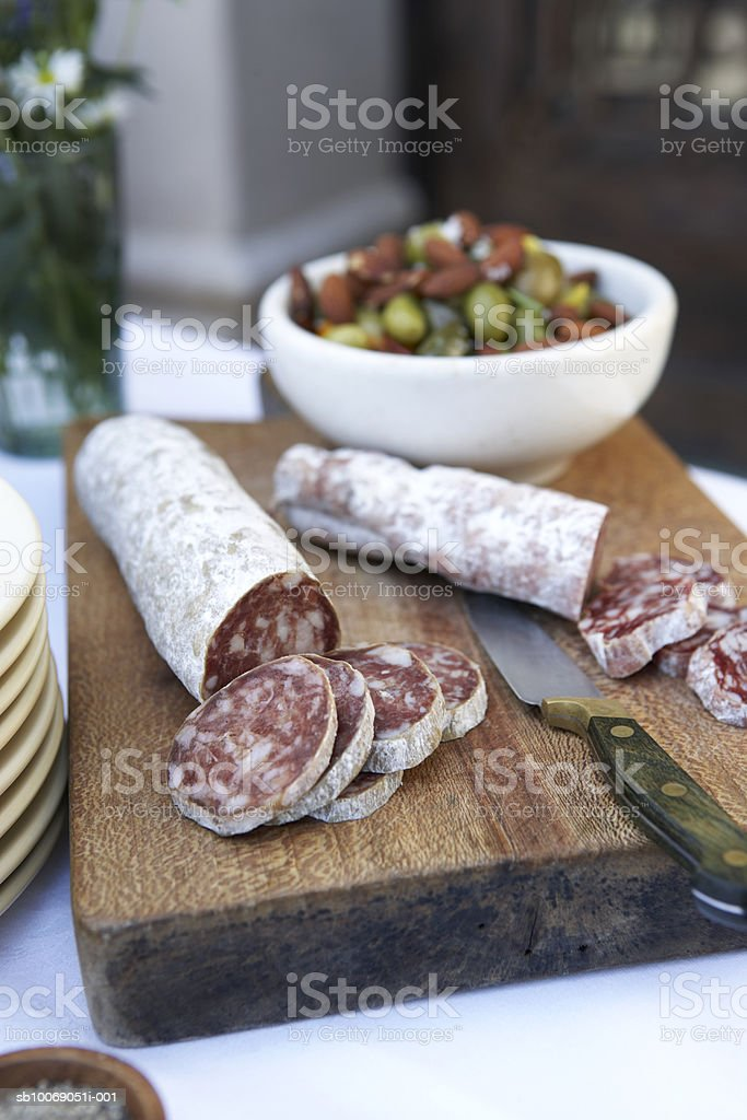 Sliced salami on cutting board with knife, bowl of olives in background, close-up royalty-free stock photo