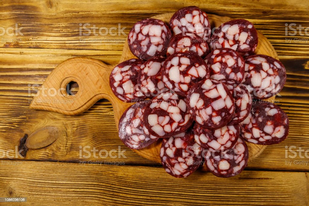 Sliced salami sausage on cutting board on wooden table. Top view
