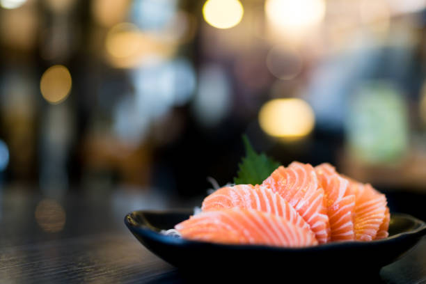 sliced salmon sashimi served on wooden table - japanese food stock photos and pictures