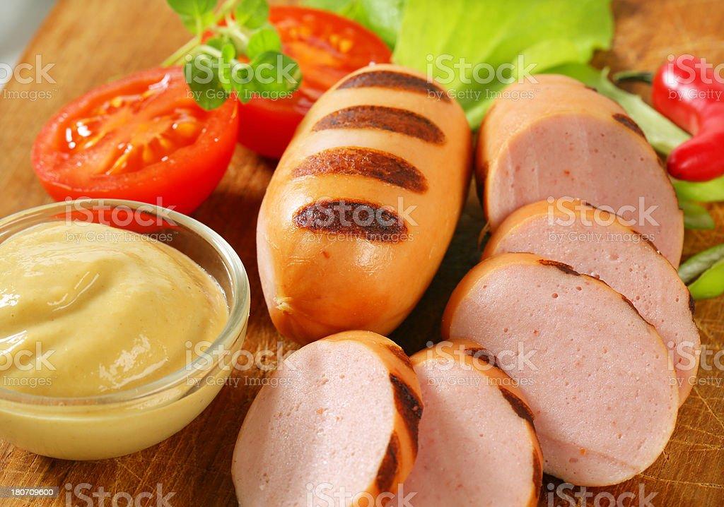 sliced sausage, mustard and vegetable garnish royalty-free stock photo