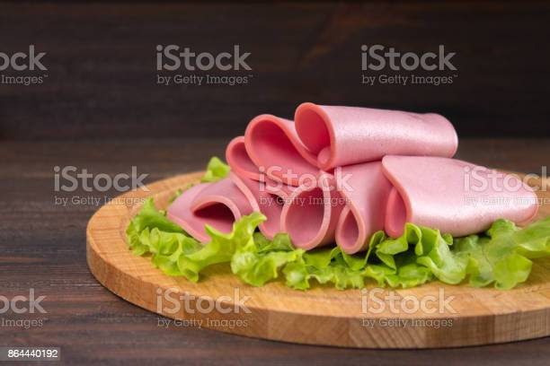 Sliced Sausages With Salad Leaves On The Wood Background - Fotografie stock e altre immagini di Alimento affumicato