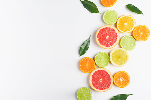 Top view of a large group of whole and sliced citrus fruits placed at the top border of a rustic wooden table. The composition includes grapefruit, orange, lemon, lime, tangerine and kumquat. Some citrus tree leaves complete the composition. High resolution 42Mp studio digital capture taken with Sony A7rii and Sony FE 90mm f2.8 macro G OSS lens