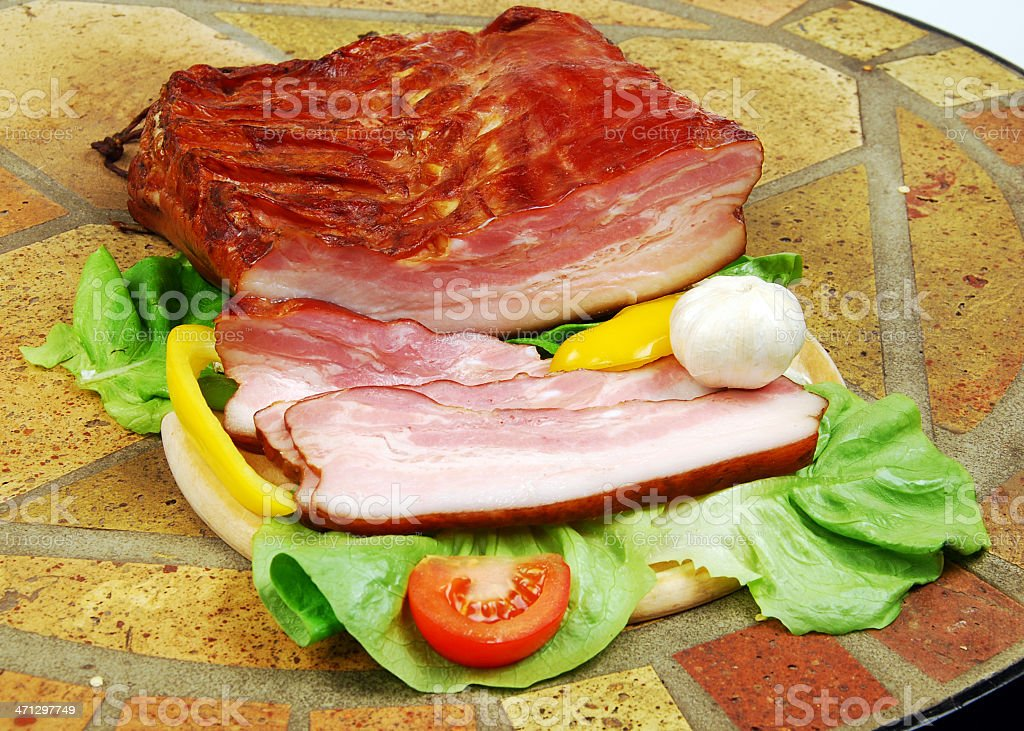 Sliced smoked bacon with wegetables. royalty-free stock photo