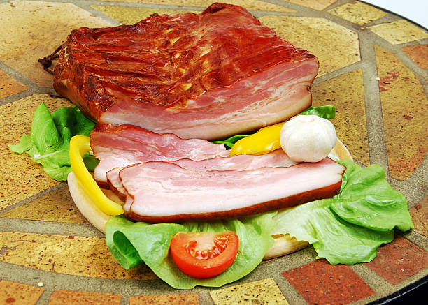 Sliced smoked bacon with wegetables. stock photo